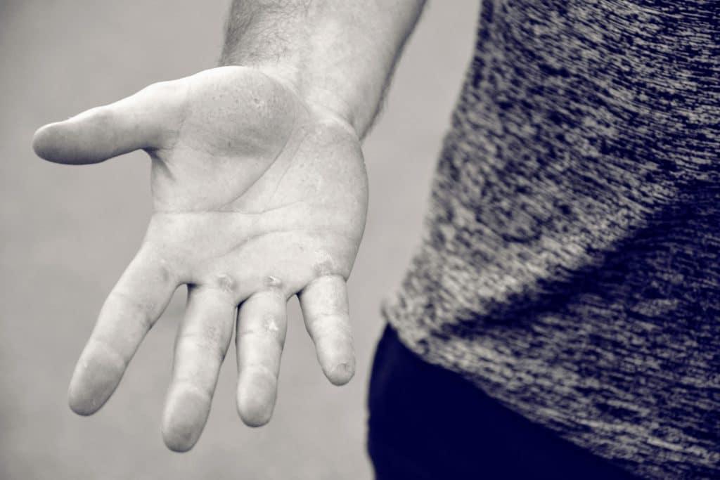Graues Shirt und eine Hand mit Schwielen